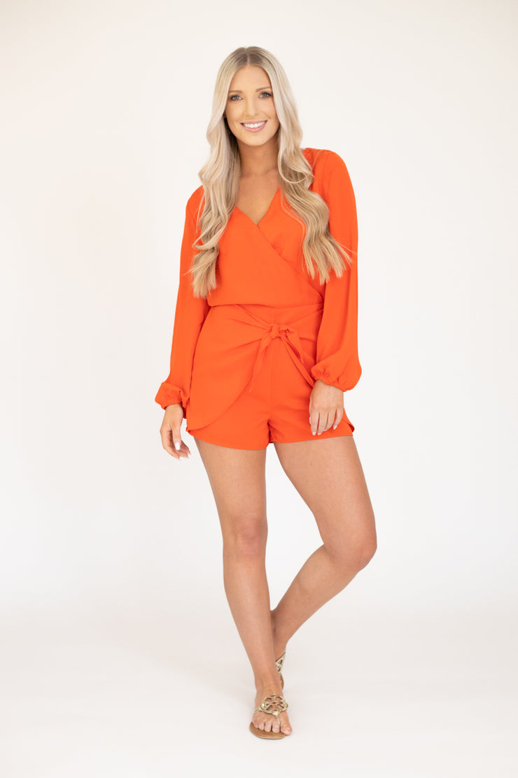 Bright red long sleeve romper with balloon like sleeves and a tie detail in front