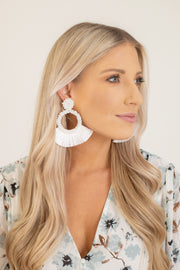 Far view of woman wearing large white circular earrings with fringe that flares out