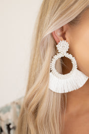 Large white detailed circular earrings with added fringe that flares off the earring