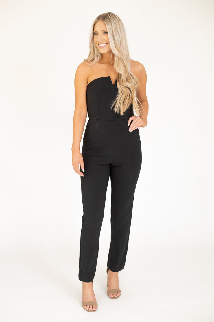 Woman wearing black strapless jumpsuit with a cut out at the top