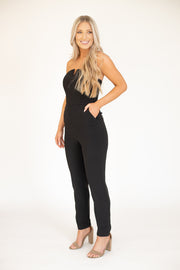 Woman wearing black flattering strapless jumpsuit with cut out at the top
