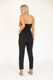 Back view of woman wearing black strapless jumpsuit