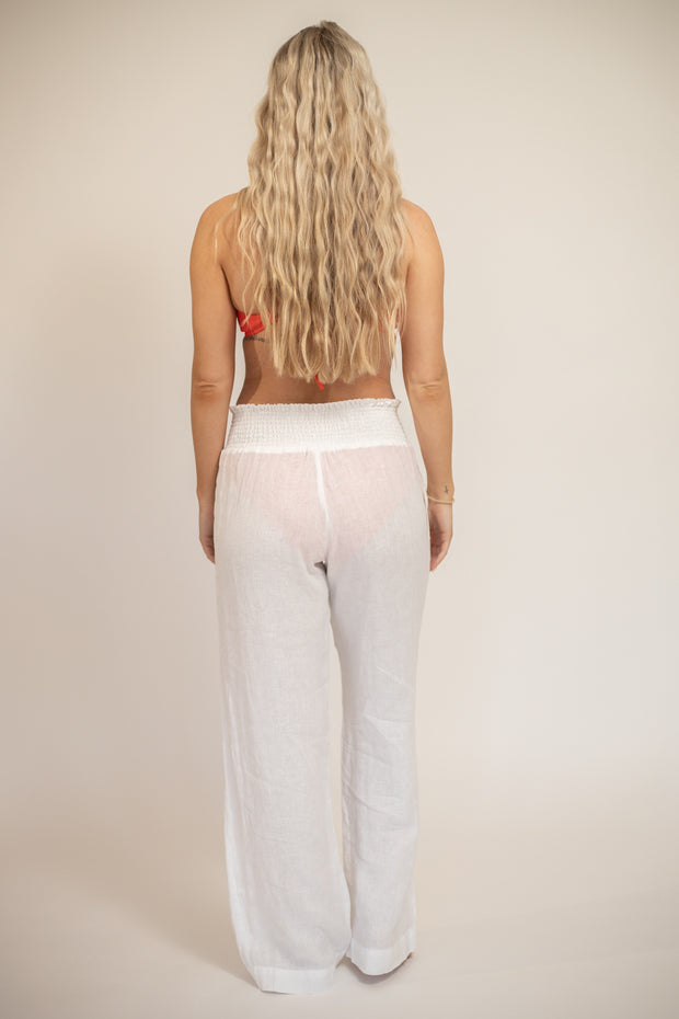 Back view of woman wearing sheer white linen pants