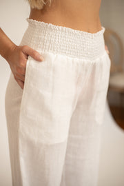 Close up of white linen pants with smocked waist and pockets