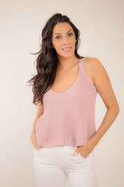 Woman wearing quartz pink tan colored A-line sweater tank with a v neck