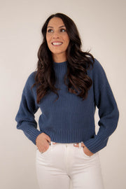 Woman wearing navy mock neck knit sweater with a slight crop feel