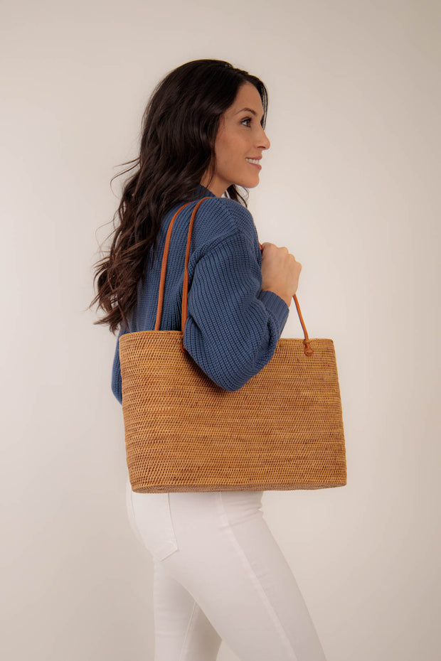 Side view of woman wearing navy knit sweater paired with a tote bag