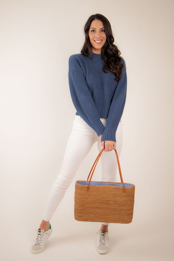 Woman wearing navy knit sweater paired with white skinny jeans
