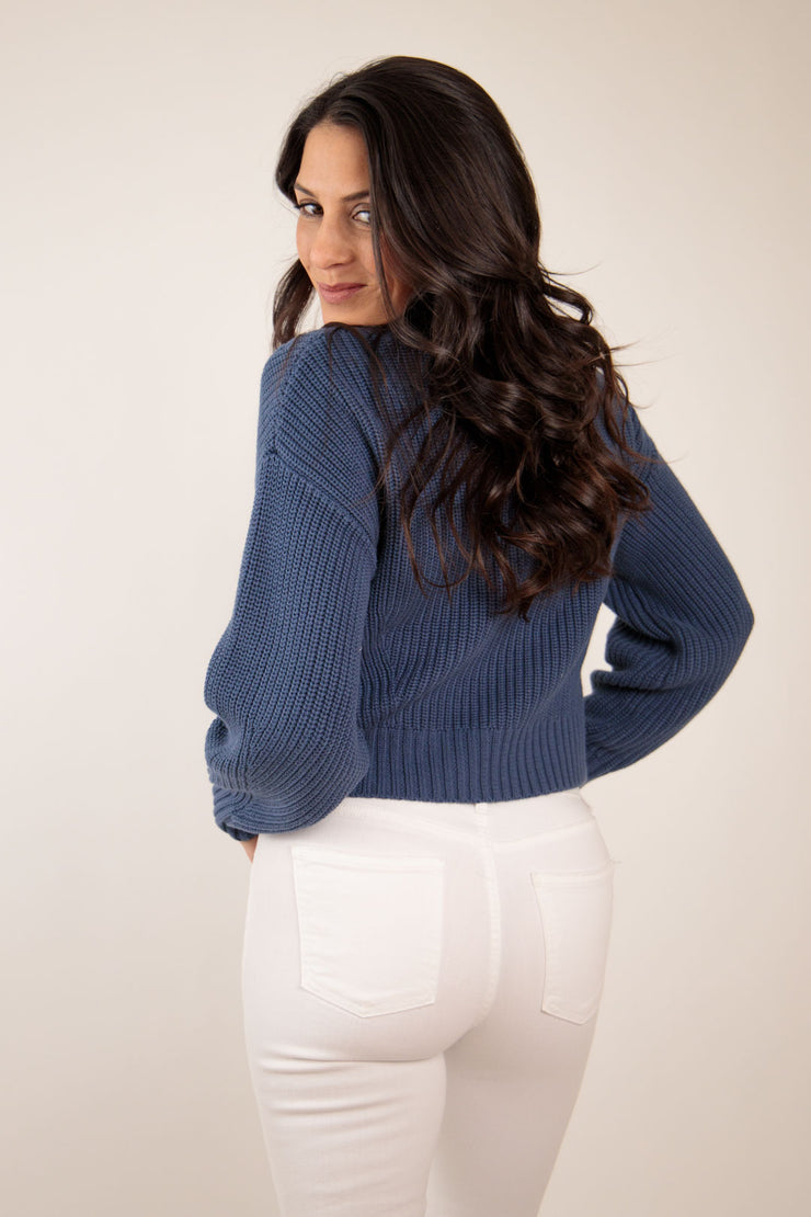 Back view of woman wearing navy knit sweater with a mock neck and slight cropped fit