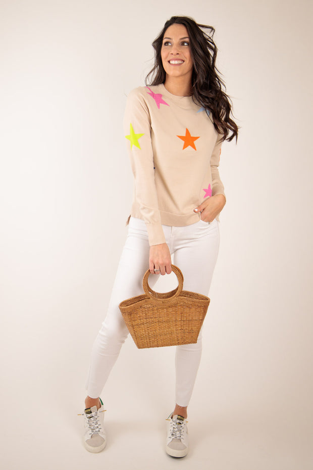Woman in neutral sweater with bright stars detailed on sweater