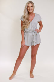 Woman wearing v neck short sleeve romper with tie detail in the front in a light grey color