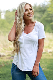Woman wearing white v neck t shirt with a slouchy pocket detail