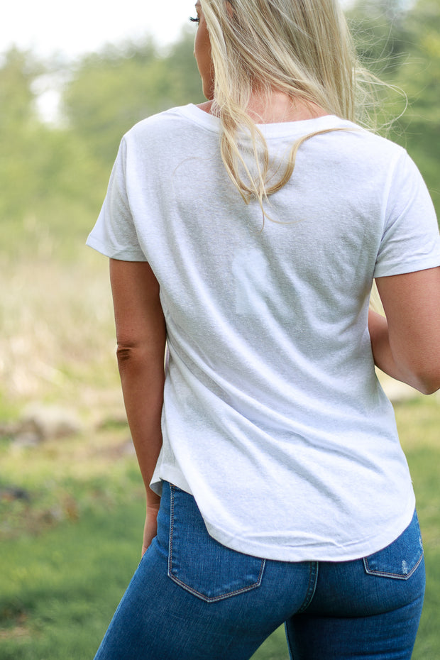 Back view of woman wearing white v neck t shirt with a looser fit
