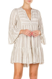 White printed babydoll fitted dress with tiered bottom, bell sleeves, and v neckline