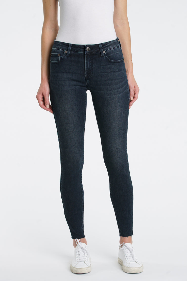 Mid rise dark skinny jeans with stretchy fabric and a raw hem