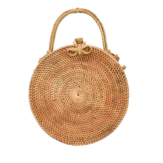 Handwoven circle bag in brown with a shoulder strap lined with palm leaves