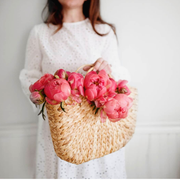 Medium sized straw tote bag with circular handles filled with pink roses