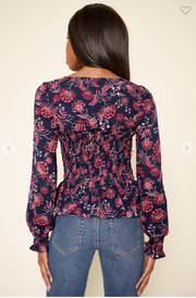 Back view of woman wearing navy and magenta floral top with square neckline, smocking detail
