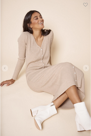Woman sitting in longs sleeve midi length dress with buttons along the front