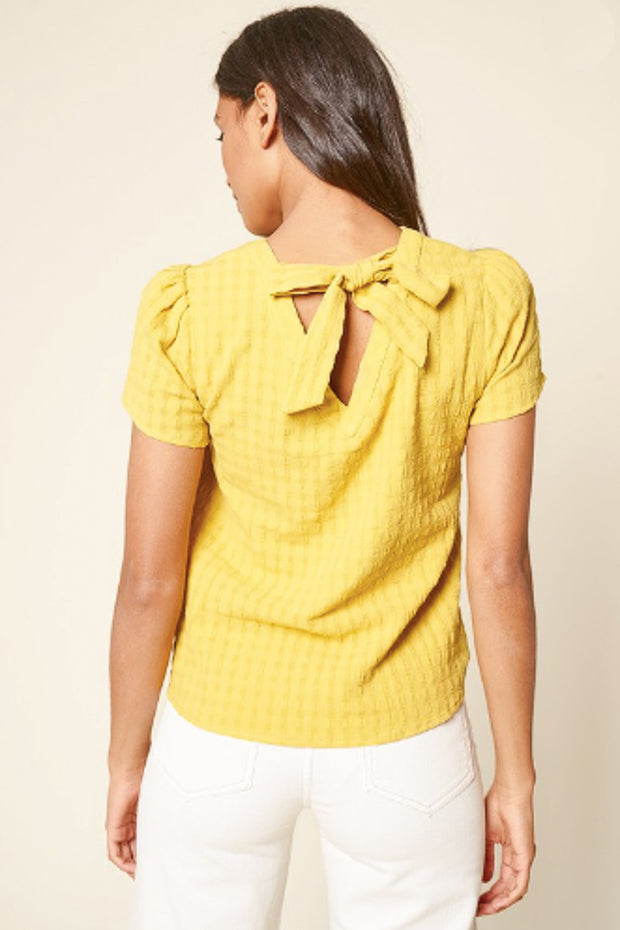 Back view of short sleeve top with tulip sleeves and a bow in the back
