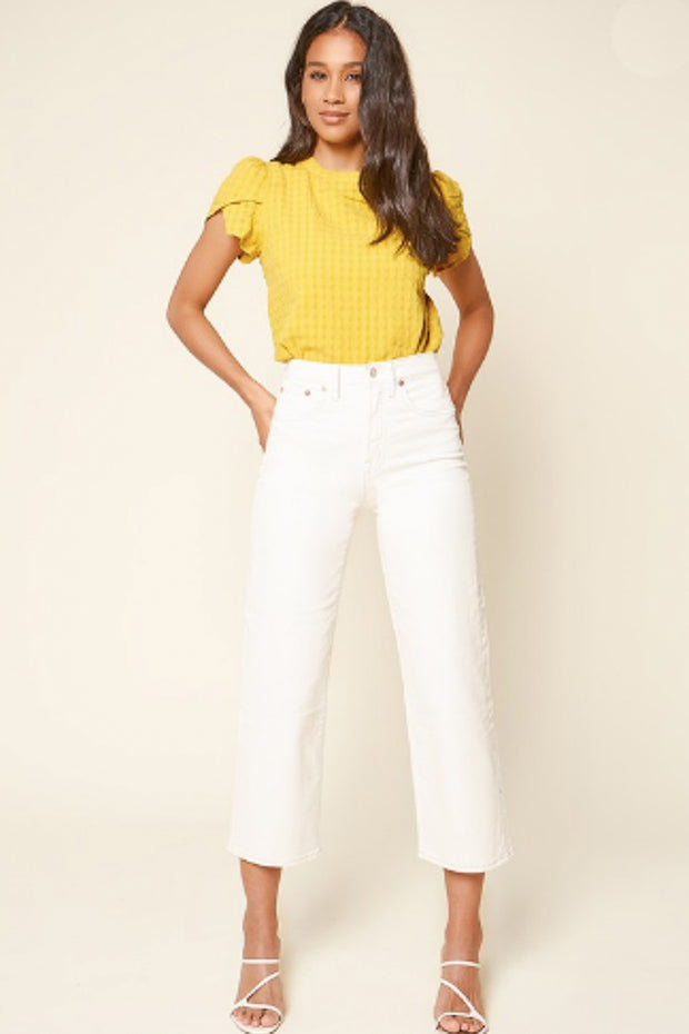 Woman wearing yellow top with white pants