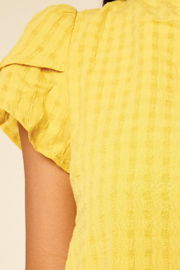 Close up of mustard yellow short sleeve top