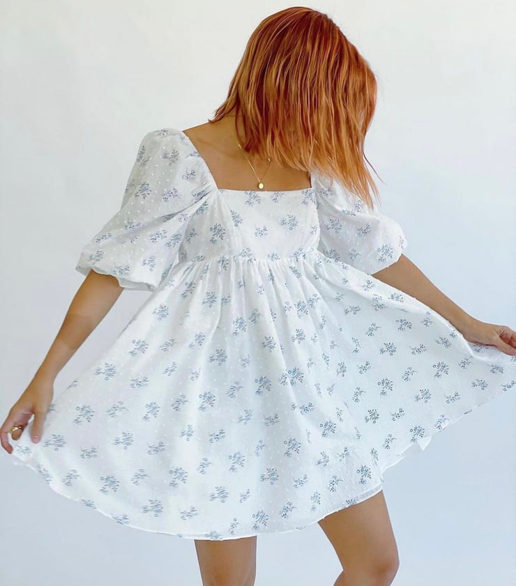 Woman wearing babydoll dress with puff sleeves in white with a blue floral print