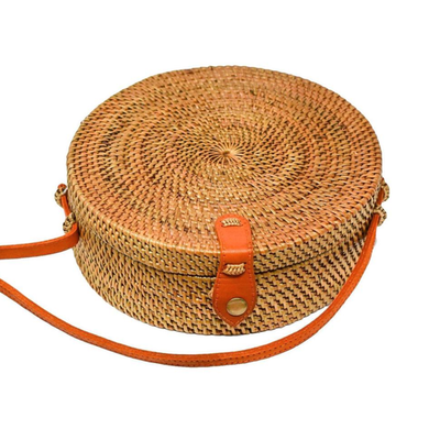 Wood woven circle bag with long orange strap lined on the inside with blue and white stripes