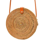 Wood woven circle bag with long orange strap lined on the inside with green palm leaves
