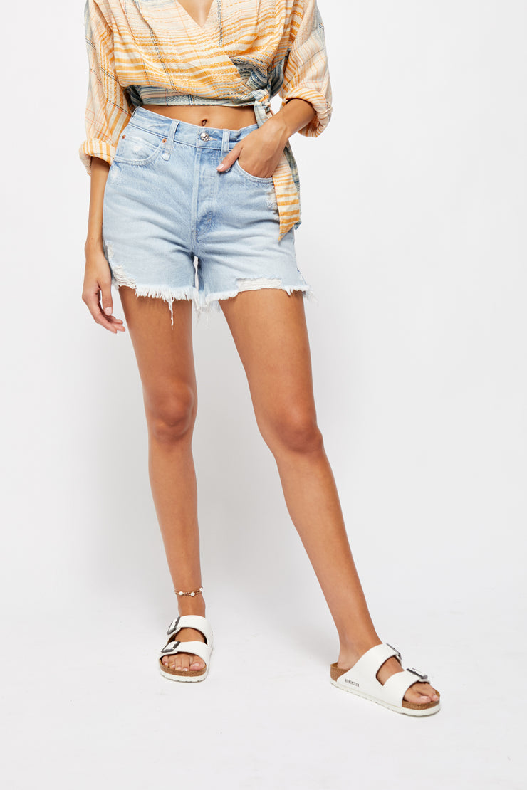 Woman wearing light wash distressed denim shorts in a high rise relaxed fit