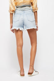 Back view of woman wearing light wash distressed denim shorts in high rise relaxed fit