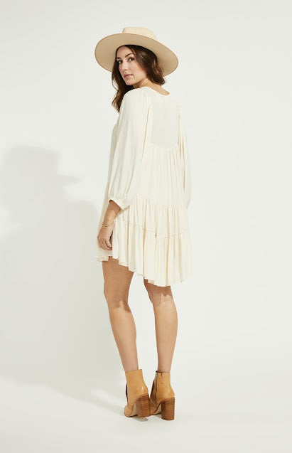 Woman wearing boho style dress with loose sleeves and a relaxed tier bottom in cream