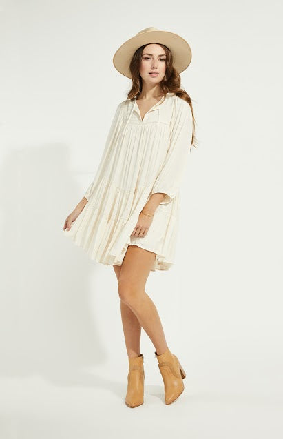 Woman standing in cream boho loose fitting dress