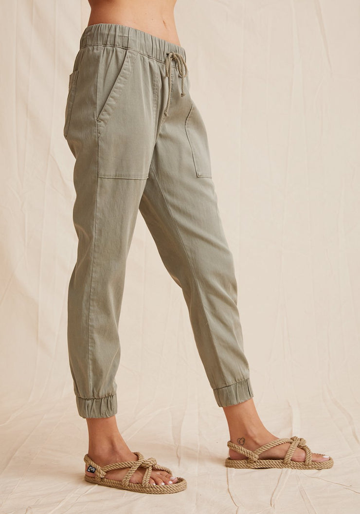 Everyday jogger in muted army green color with tie waist, cuffed bottoms, and pockets