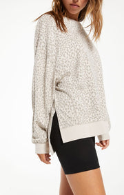 Woman wearing muted leopard print pullover with side slits
