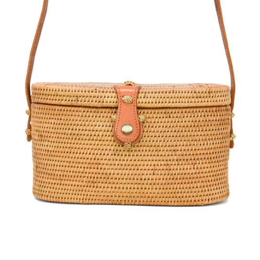 Oval shaped top-close style bag with shoulder strap in a woven straw rattan