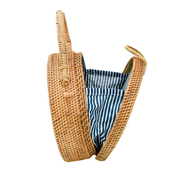 Handwoven circle bag with woven bowtie latch and lined inside with navy stripes