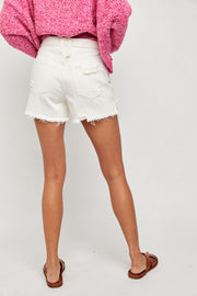 Back view of woman wearing white high rise distressed denim shorts