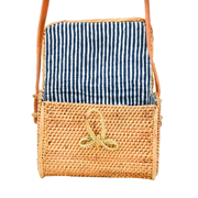 Handwoven messenger style purse with woven bowtie latch and lined with navy and white stripes