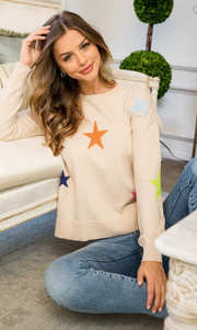 Woman sitting in neutral colored sweater with bright stars