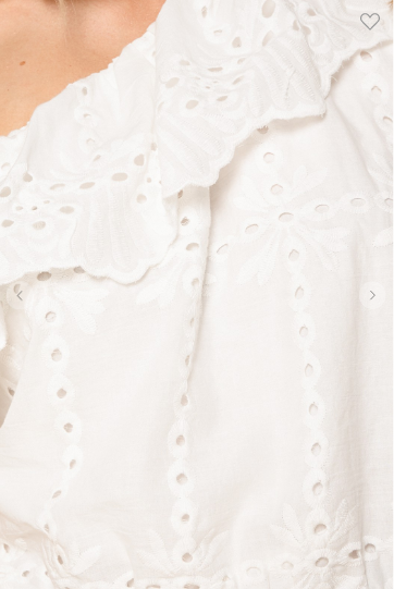 Close up of one shoulder ruffling in the embroidered eyelet