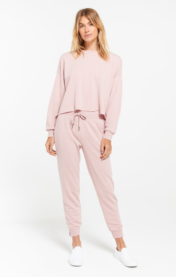 Woman wearing pink joggers in a french terry fabric with ribbed detail on the ankles and waistband