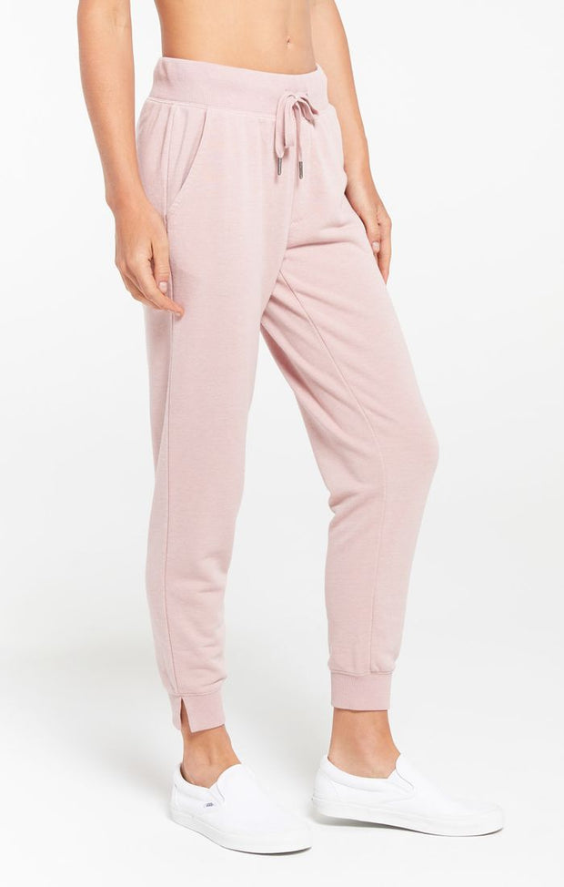 Woman wearing french terry jogger with tie waist and cuffed bottoms in pink