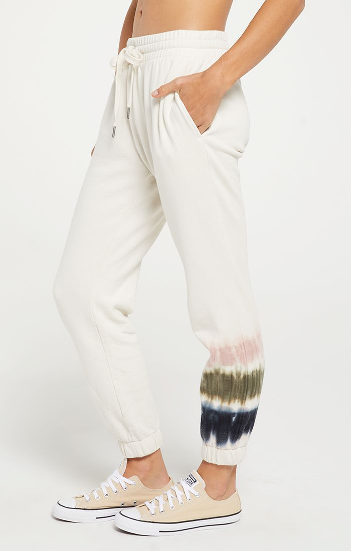 White jogger with small tie dye print on one bottom of the joger, cinched ankles and tie waist