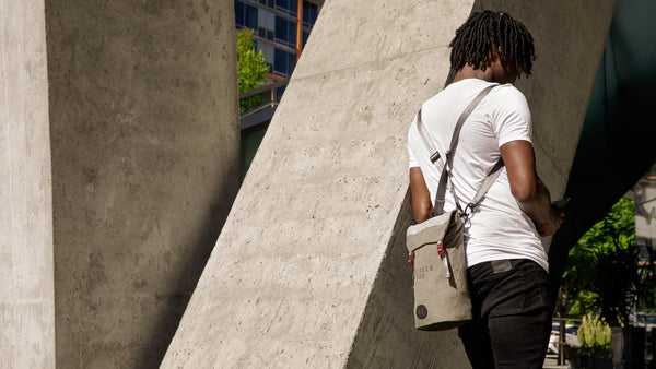 Man leans against wall with Fierce Hazel Backpack on his back