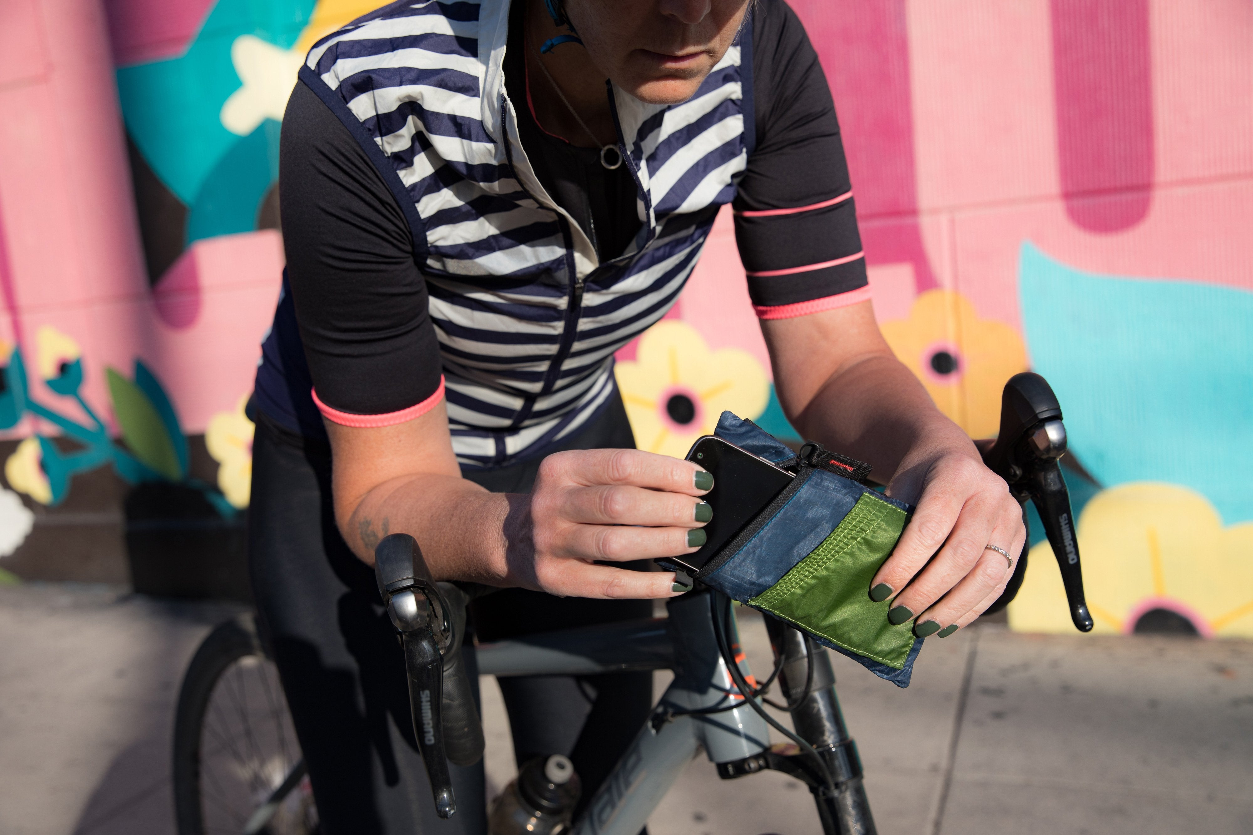 Person with bike pulling out a smart phone from cycling wallet