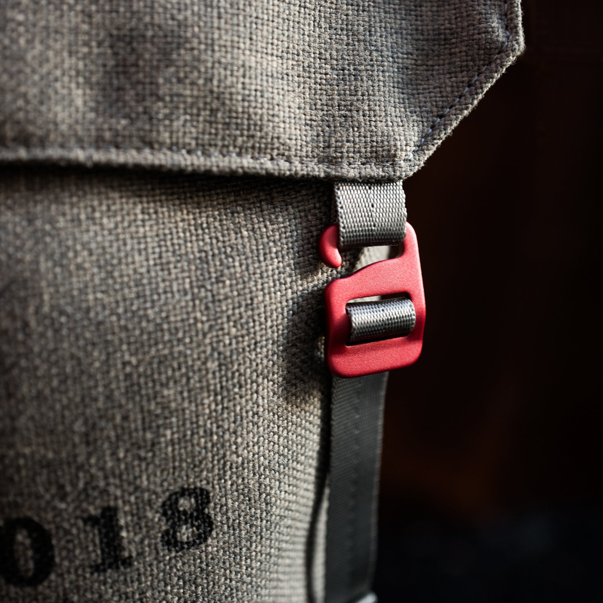 Close-up of red anodized aluminum clip on a Fierce Hazel convertible small messenger bag made with sustainable fabric. Functional, rugged and water-resistant it is military styled but beautiful