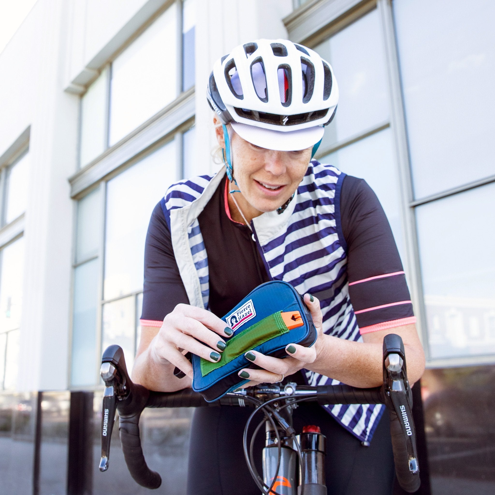 Woman cyclist using a weatherproof, sustainable cycling wallet.
