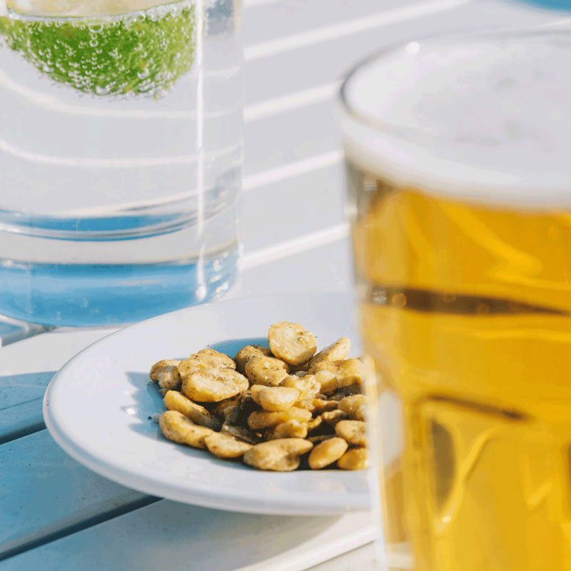 pulsitos fava bean snacks next to a cold refreshing beer