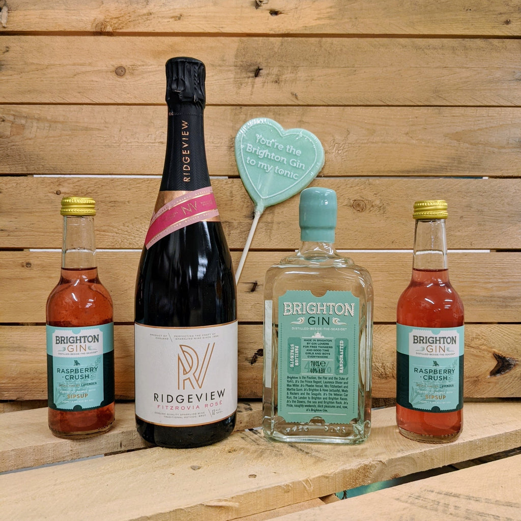 The lineup of the gift hamper consisting of 700ml Brighton Gin Pavilion Strength, a bottle of Ridgeview, 2 bottles of ready-to-drink Raspberry Crush and and a Brighton Gin lolly.